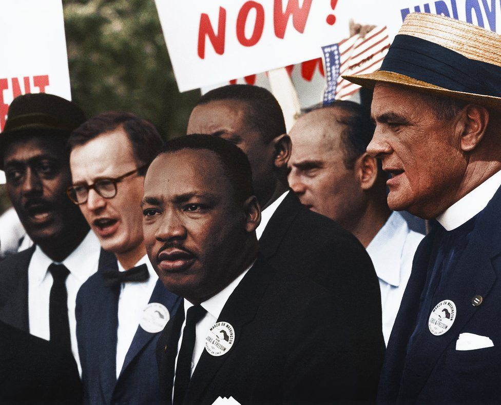 Dr. Martin Luther King stands with others at a march in a colourised photo