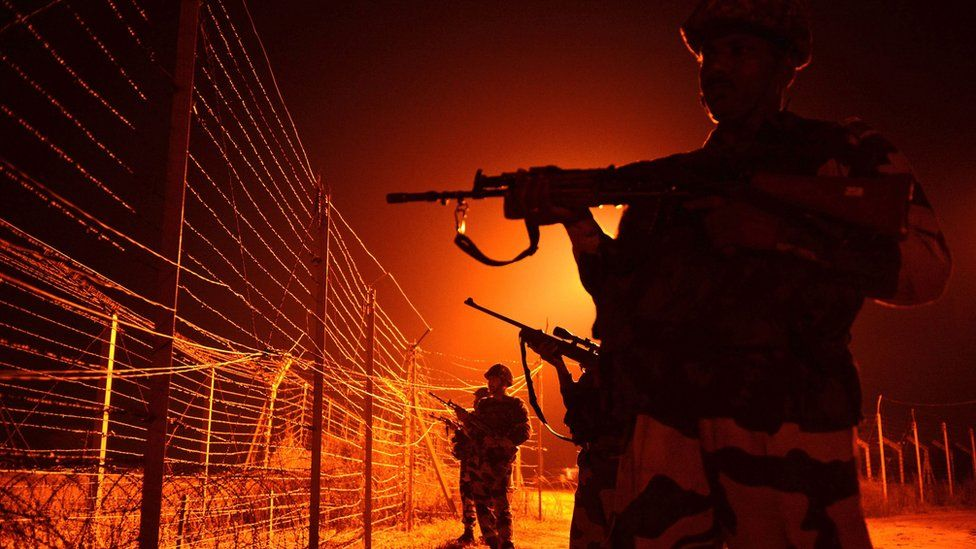 In this file photograph taken on January 17, 2013, Indian Border Security Force (BSF) soldiers patrol along a border fence at an outpost along the Line of Control (LOC) between India-Pakistan at Abdulian, some 38 kms southwest of Jammu