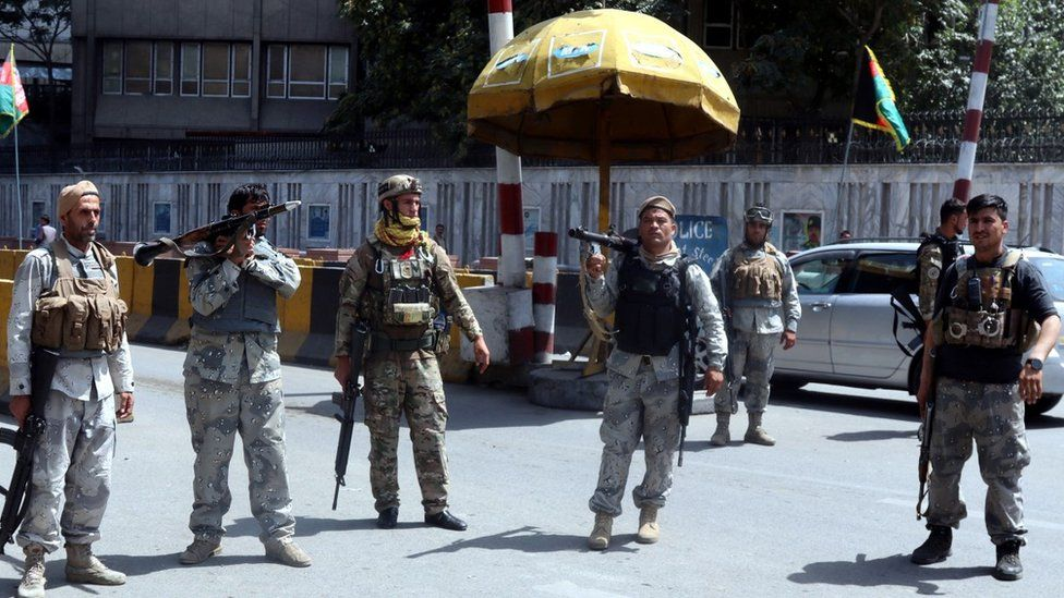 Afghan security officials stand guard at a checkpoint in Kabul, Afghanistan, 15 August 2021