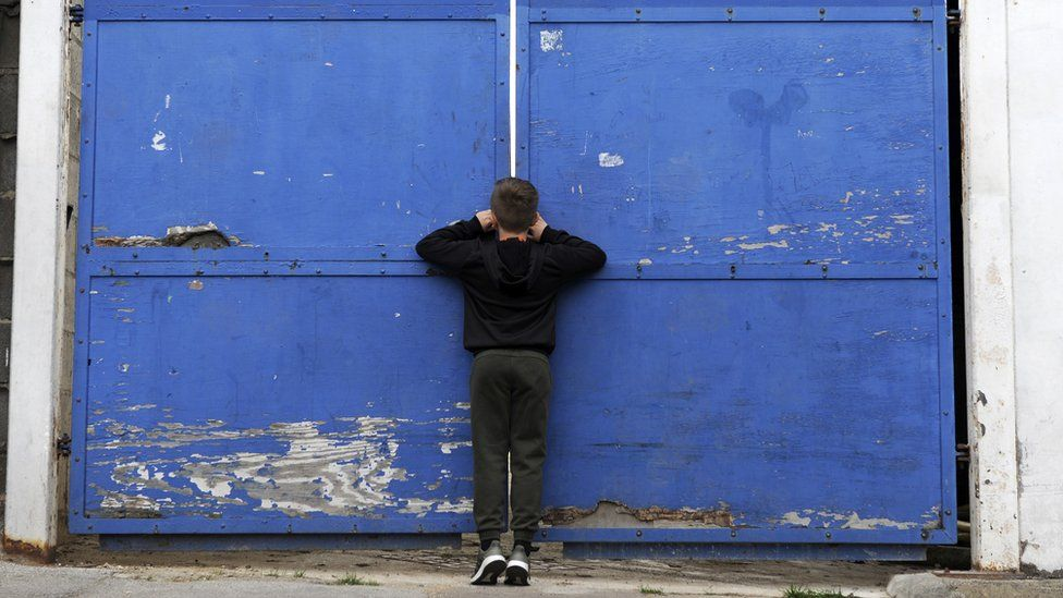Young fan peers through a gate at Kenilworth Road