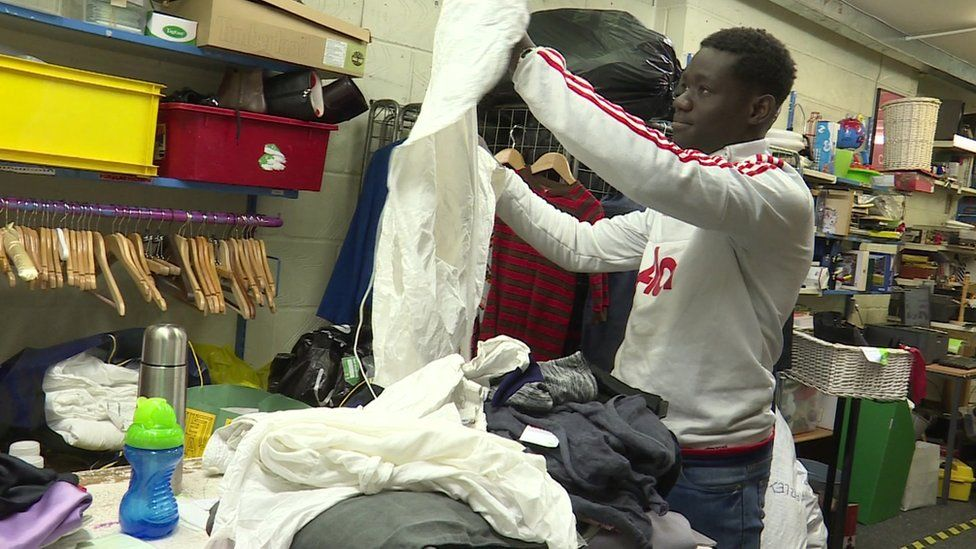 Man sorting clothes in Oxfam store