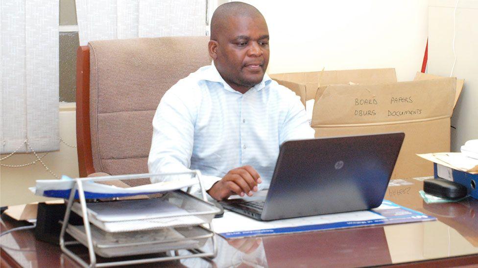 Gospel Mavutula behind his desk in the office.
