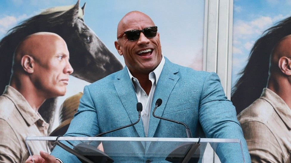 The Rock speaks at a podium during his latest film release