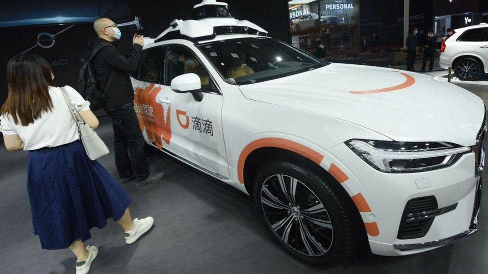 Visitors look at Didi's new generation of driverless cars at the Shanghai Auto Show in Shanghai, China.