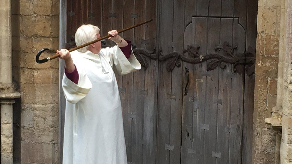 Bishop June Osborne knocking at the door of Llandaff Cathedral