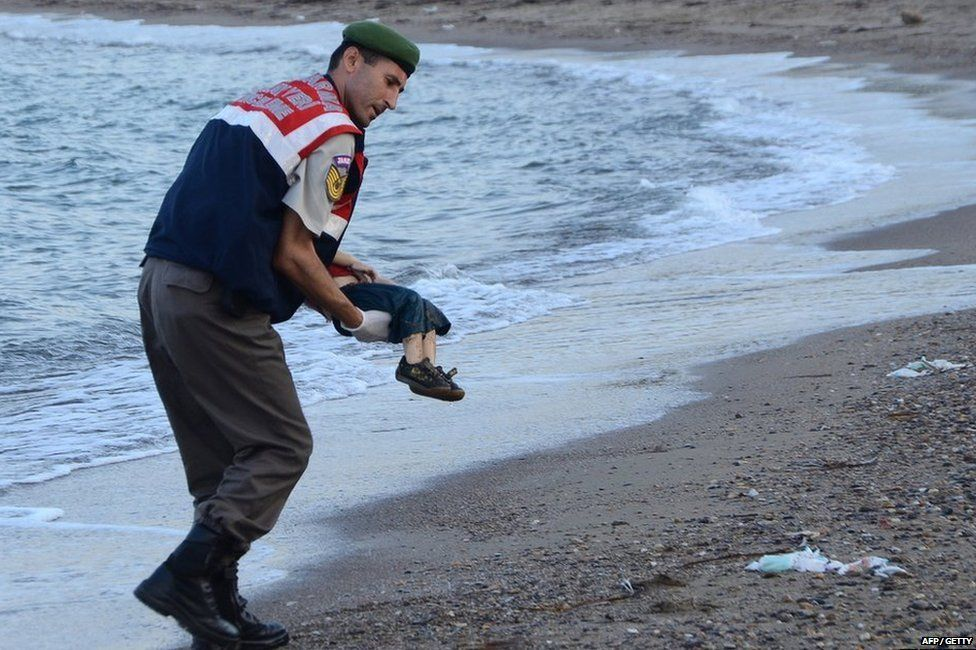 Body of Aylan Kurdi being lifted out of the water