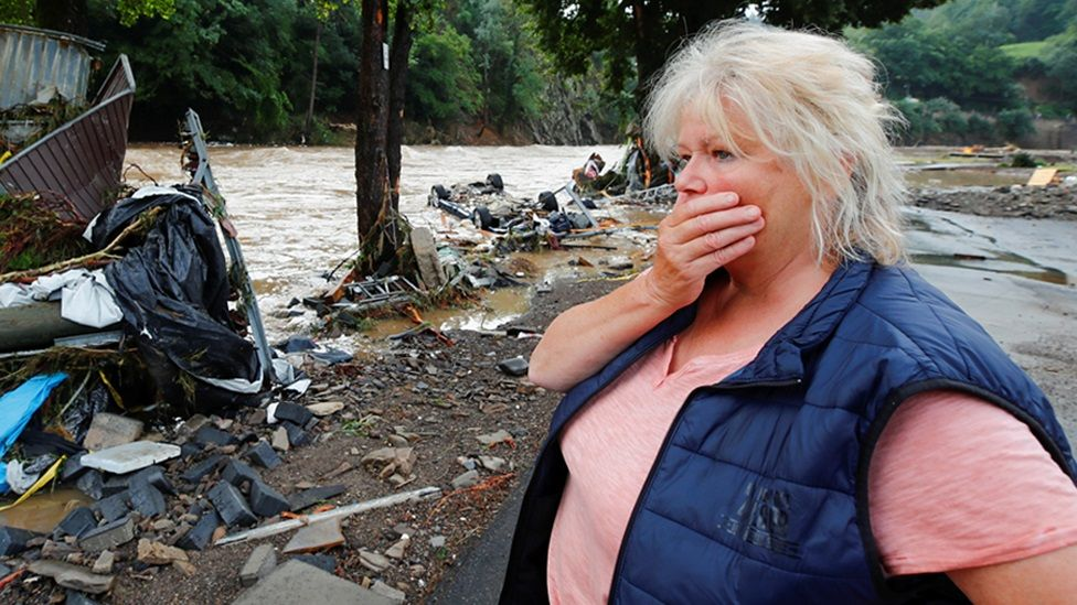 A woman looks at debris brought by the flood next to the Ahr river