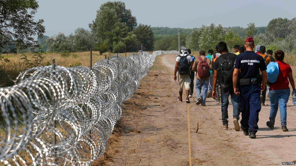 A policeman escorts migrants on the Hungarian-Serbian border in Asotthalom, Hungary on 13 August 2015