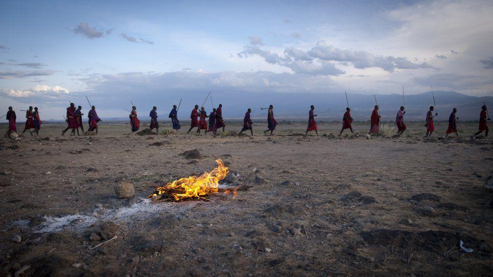A row of Maasai walk behind a fire