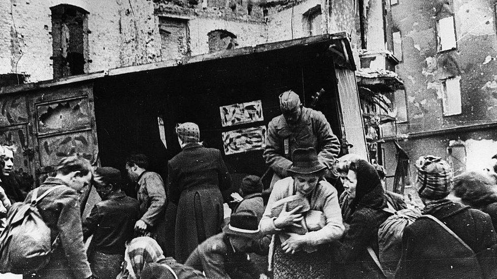 Soviet soldiers hand out bread to civilians in Berlin 1945