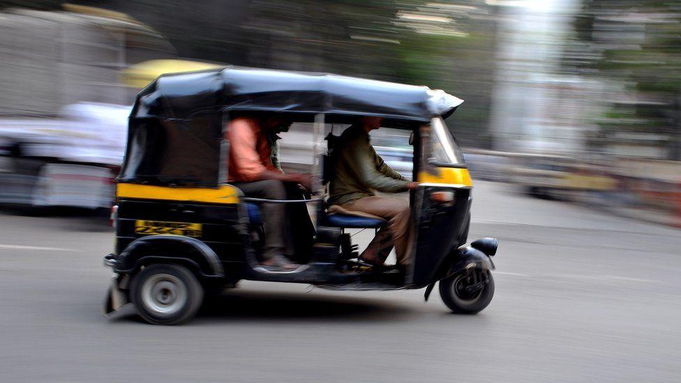 Auto-rickshaw speeding down street