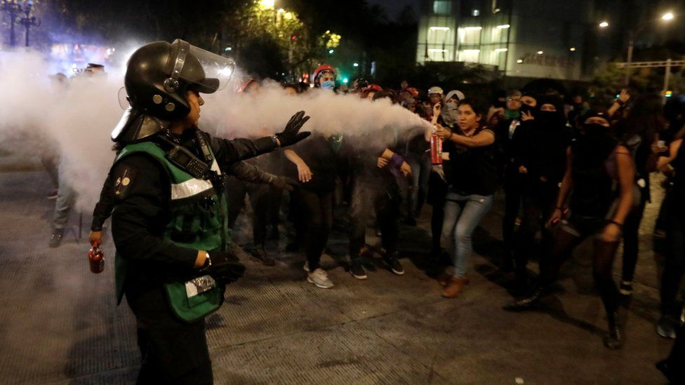 A demonstrator aims a fire extinguisher towards a police officer during a protest against femicide and violence against women, in Mexico City, Mexico, 25 November 25.