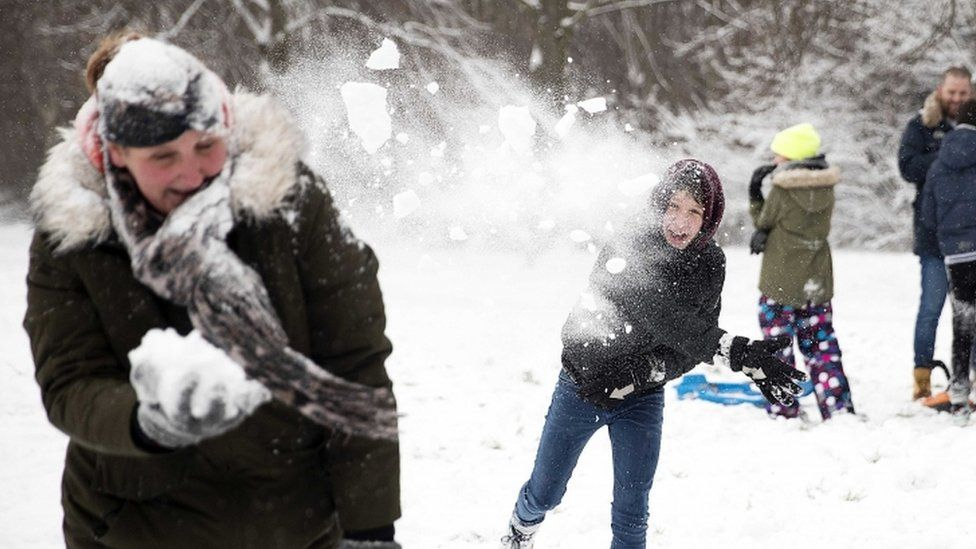 People throw snowballs at each other as they enjoy the snow on a hill in Rotterdam