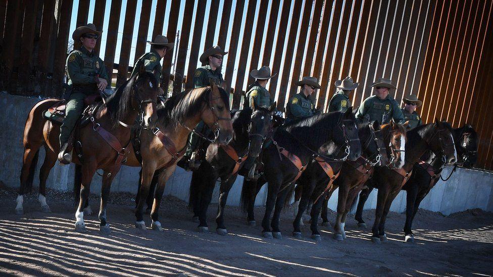 Border Patrol officers at the US border wall