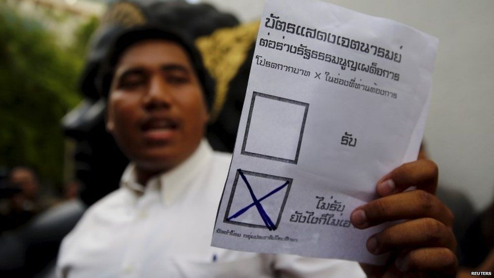 An opposition student holds up a mock ballot paper in Thailand