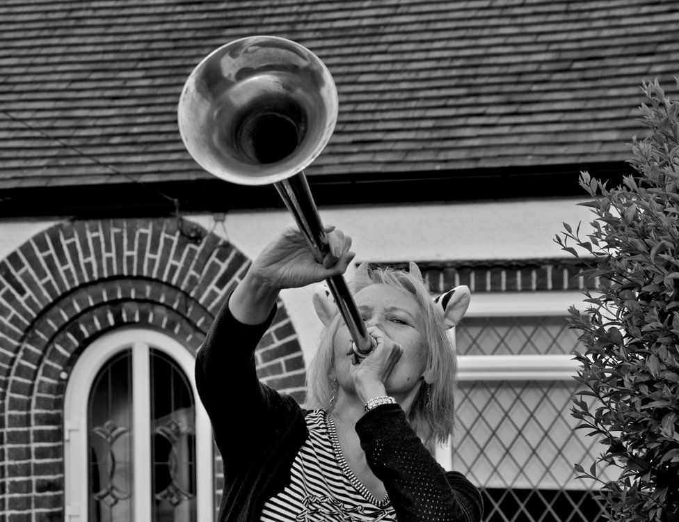 Woman blowing a horn