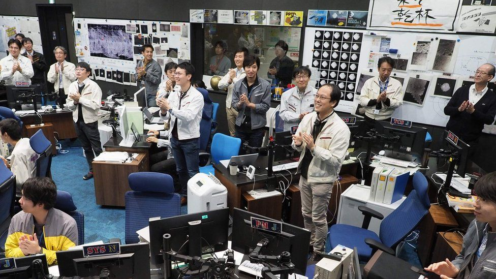 Jaxa scientists and staff smile and clap their hands from mission control