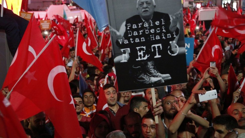 Supporters of Turkish President Recep Tayyip Erdogan wave their national flags and hold a portrait of Fethullah Gulen