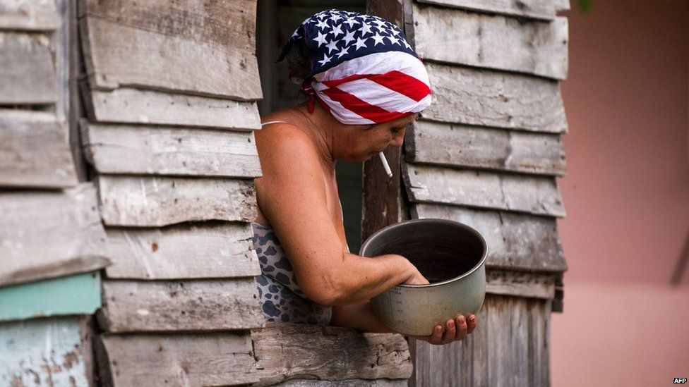 A woman wearing a headscarf with a US flag design works at her house in Havana on 1 July, 2015