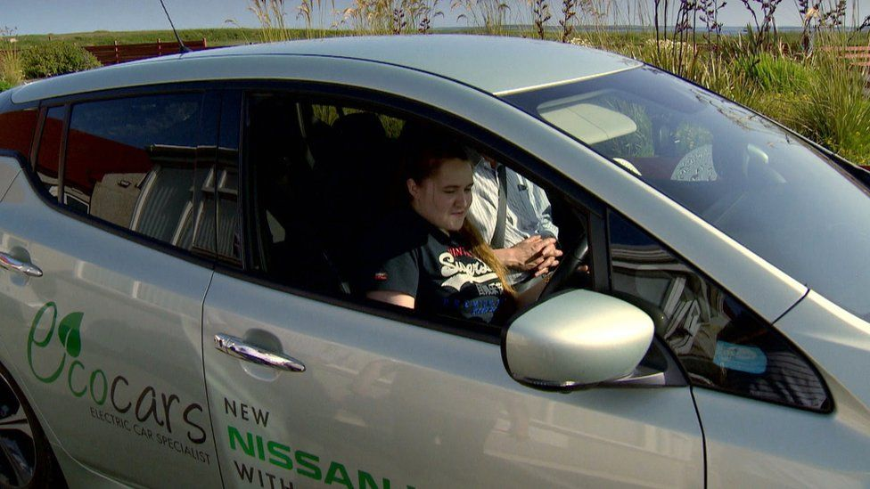 Charlotte testing an electric car