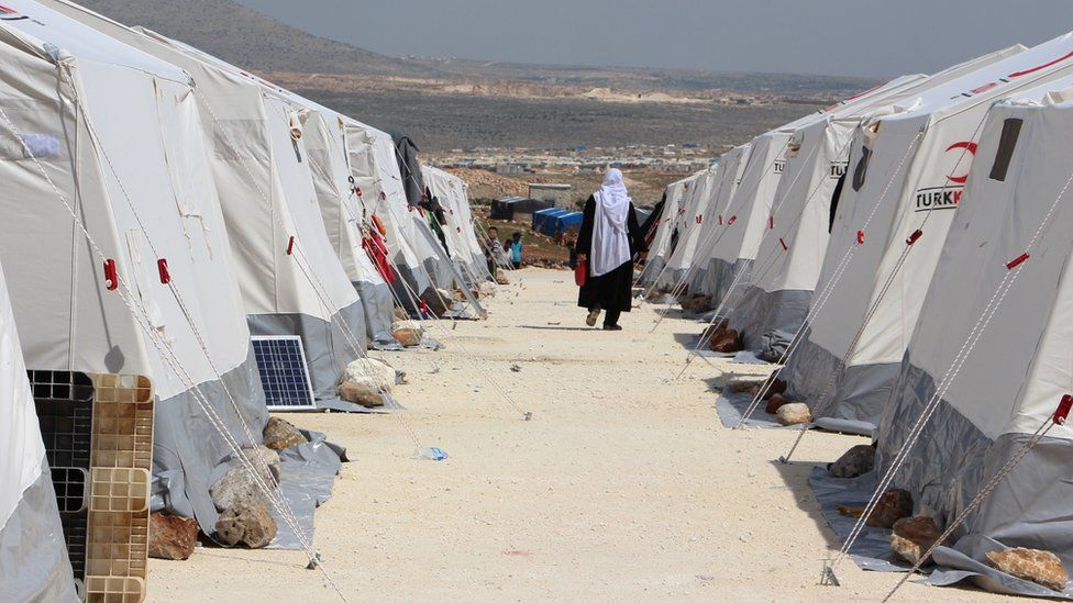 A Syrian woman, evacuated from the Eastern Ghouta, walks between tents at a camp for displaced people in Kafr Lusin, in Idlib province, on 1 April 2018