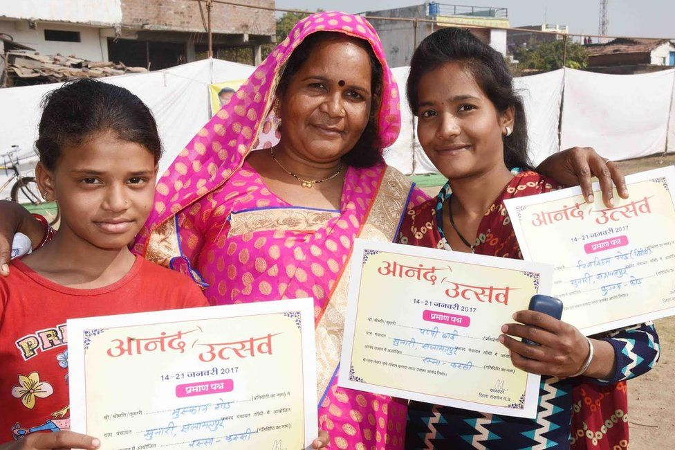 """A woman and two girls show the certificates they received on """"happiness day"""""""