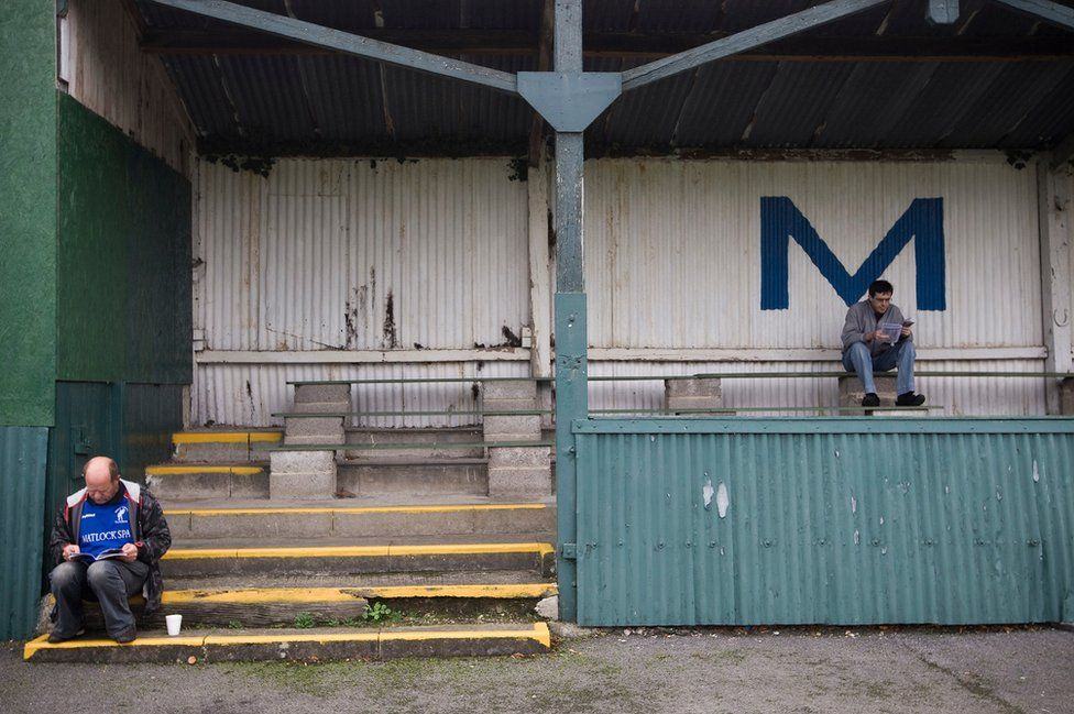 Two Matlock Town fans reading the matchday programme