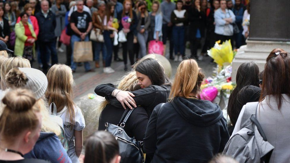 Two women hug during minute's silence