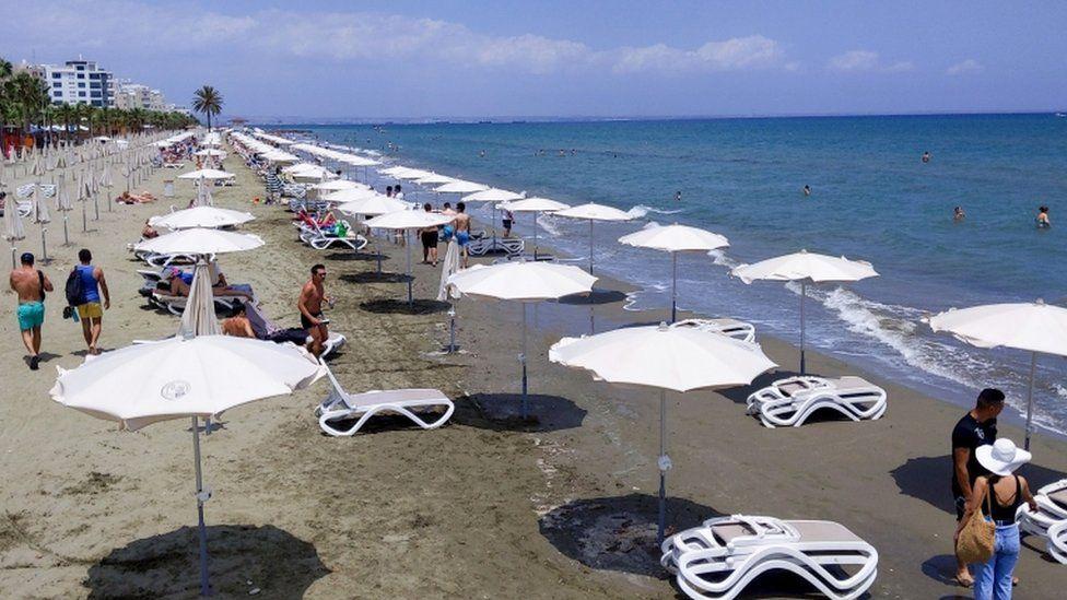 People walking along a beach in Cyprus