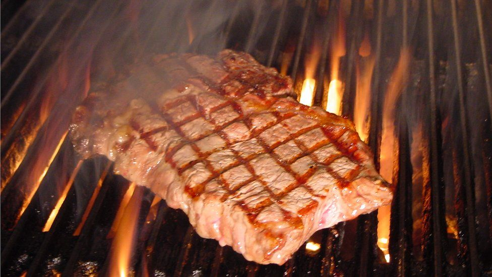A steak cooking on a grill