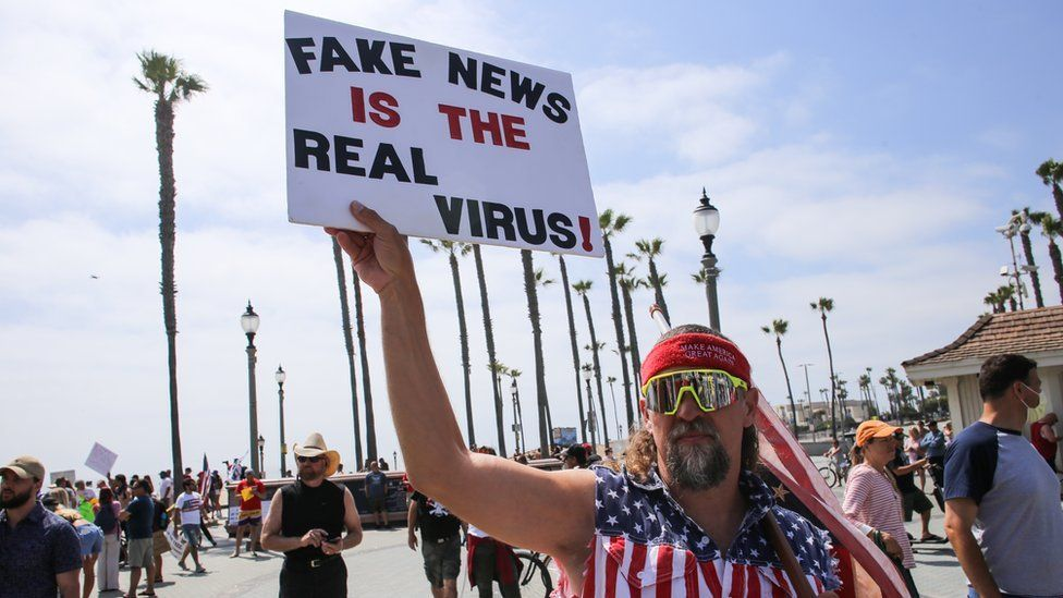 """A man holds a sign during a demonstration in California in early May saying """"Fake news is the real virus"""""""