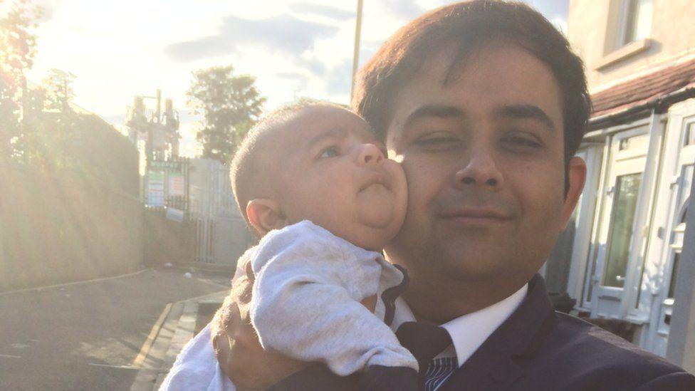 Waseem Iqbal holding his son Muhammad