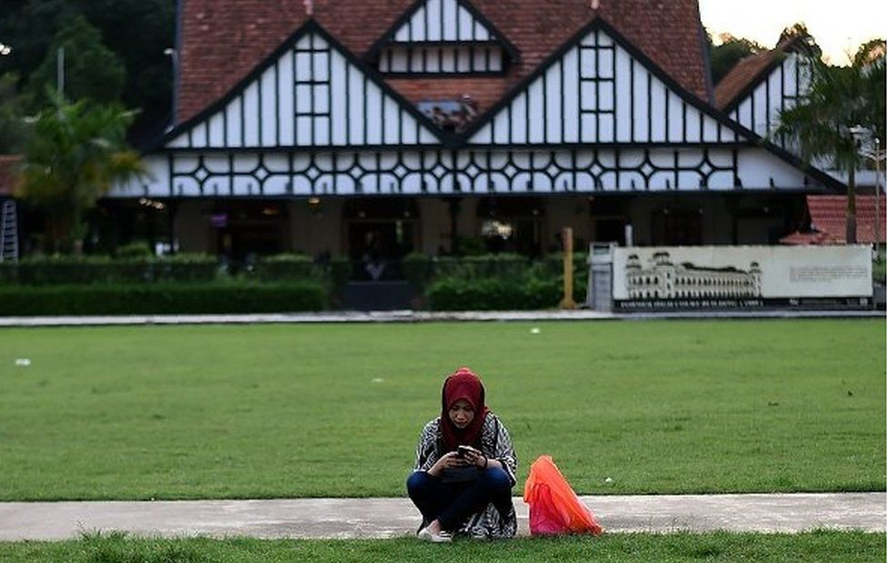 A Malaysian Muslim girl sits in an open field at Independence Square in Kuala Lumpur on June 28, 2017.