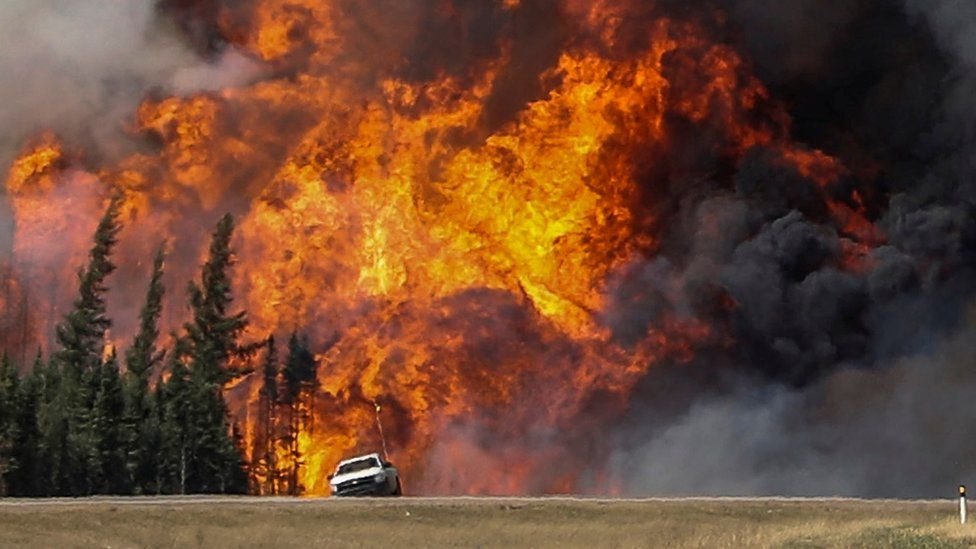 A car parked in front of a huge wildfire in Canada