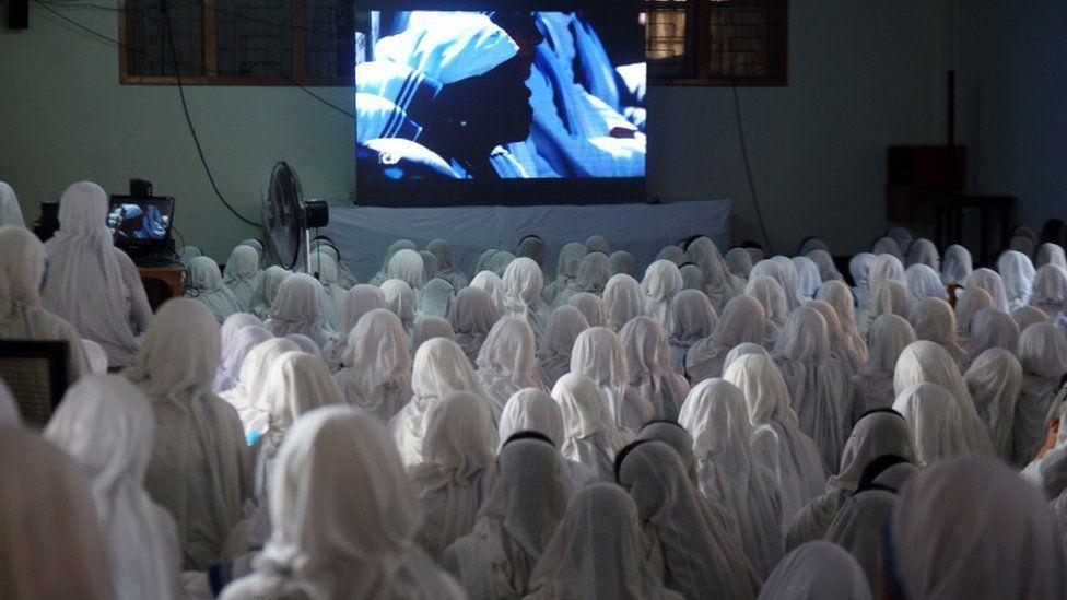 Nuns in Kolkata watch the ceremony