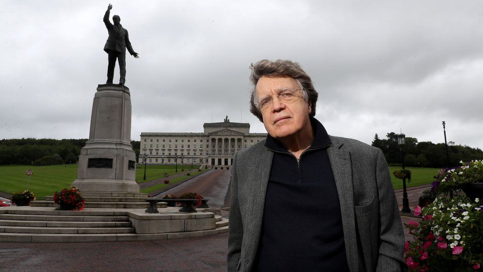 Caption: Merlin Holland, grandson of Oscar Wilde, at the statue of Edward Carson outside Parliament Buildings in Belfast, during filming for Edward Carson And The Fall Of Oscar Wilde