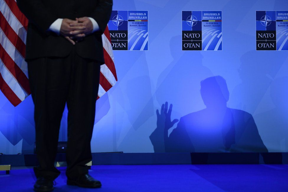 US Secretary of State Mike Pompeo (left) looks on as US President Donald Trump casts a shadow as he addresses a press conference on the second day of the North Atlantic Treaty Organization (NATO) summit in Brussels