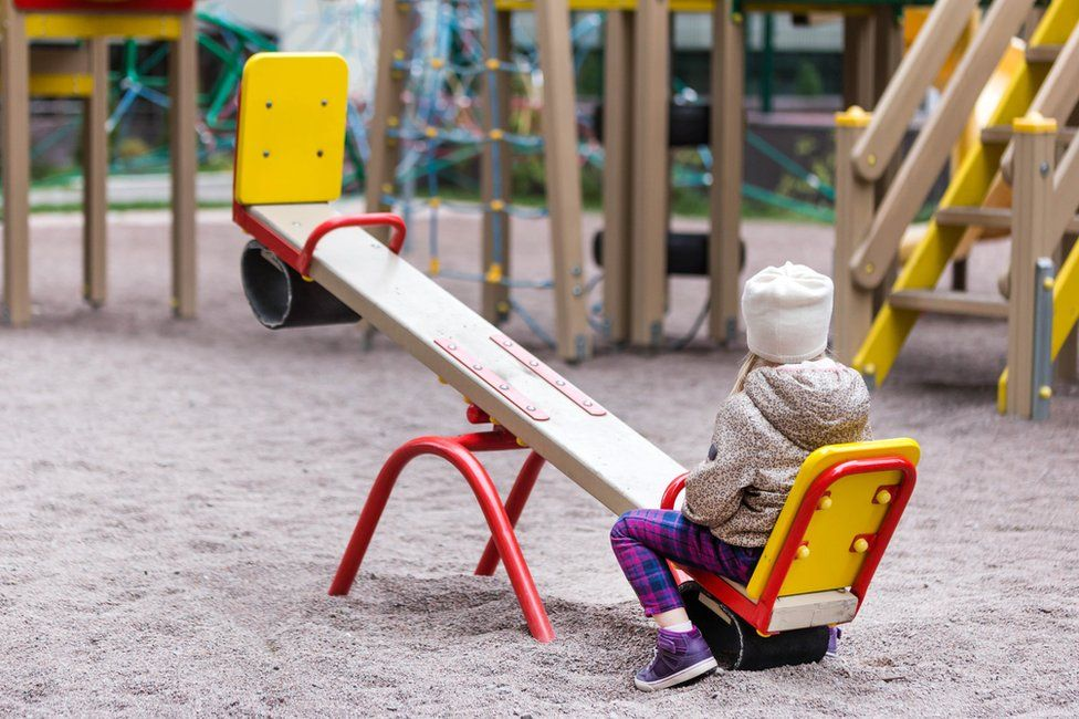 A girl sits at one end of a seesaw