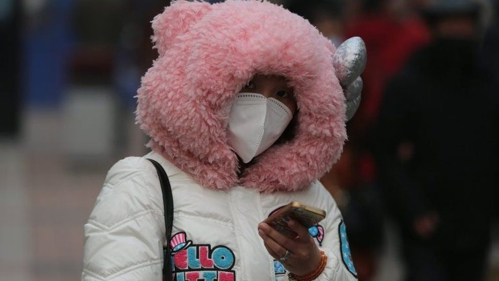 A Chinese woman wearing mask walks in a shopping street during a hazy day in Beijing city, China, 22 December 2015
