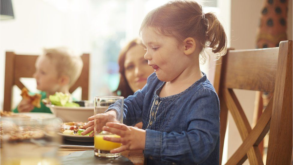 A young girl takes a big drink of orange juice during a meal