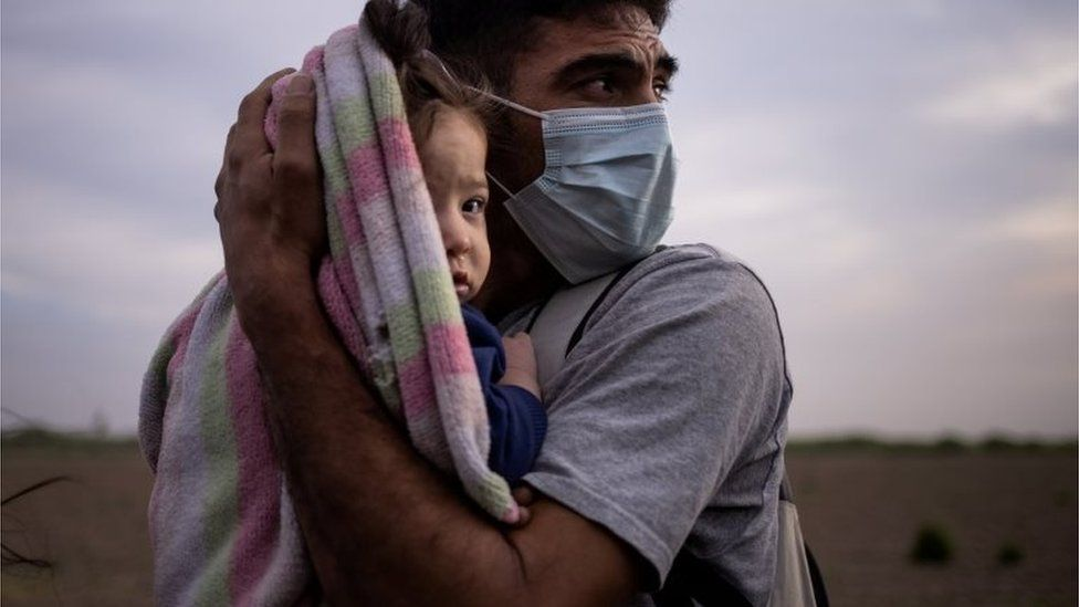 An asylum seeker holds his daughter as they await transportation to a processing centre in the US