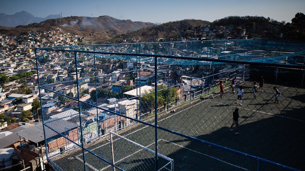 A view of the caged football pitch as the girls train, with a sweeping view of the hilly favela shanty town landscape visible beyond it
