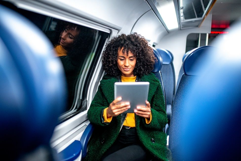 Woman using wi-fi device on train