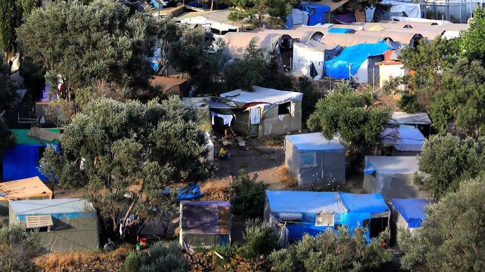 A view of a makeshift camp and the formal camp for refugees and migrants over the town of Vathy on the island of Samos, Greece, 1 July 2019