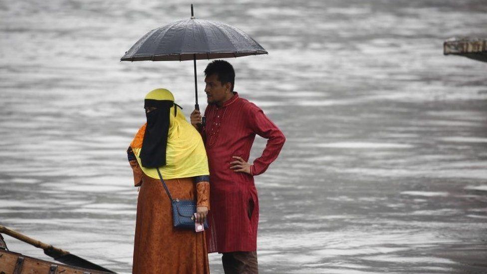Bangladeshi passengers use an umbrella as they cross the Buriganga River by boat during a rainy day in Dhaka, Bangladesh