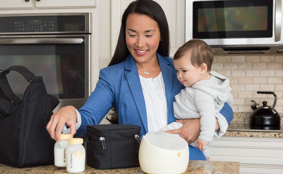 Woman with baby preparing expressed milk bottles