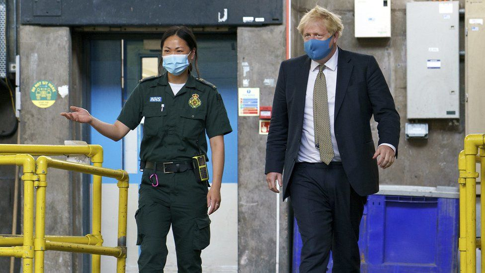Boris Johnson wears a mask during a visit to London Ambulance Service