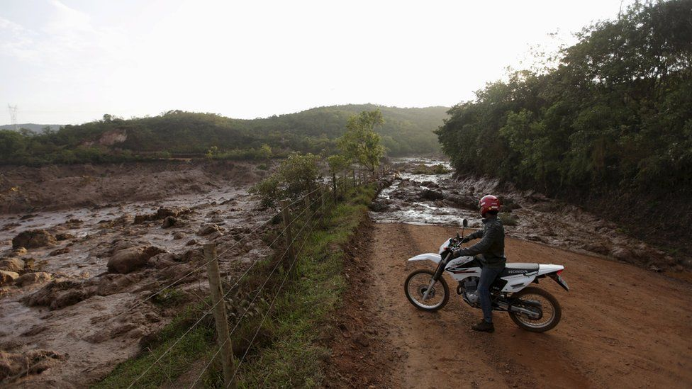 A man on a motorbike inspects the mud across the road.