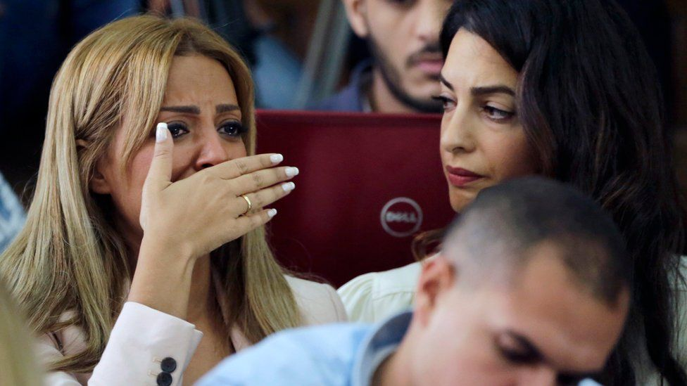 Marwa Omara (left) is comforted by Amal Clooney after Mohamed Fahmy and Baher Mohamed are convicted by a court in Cairo (29 August 2015)