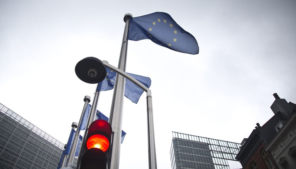A red light flashes in front of an EU flag in front of EU headquarters in Brussels on Friday, June 24, 2016